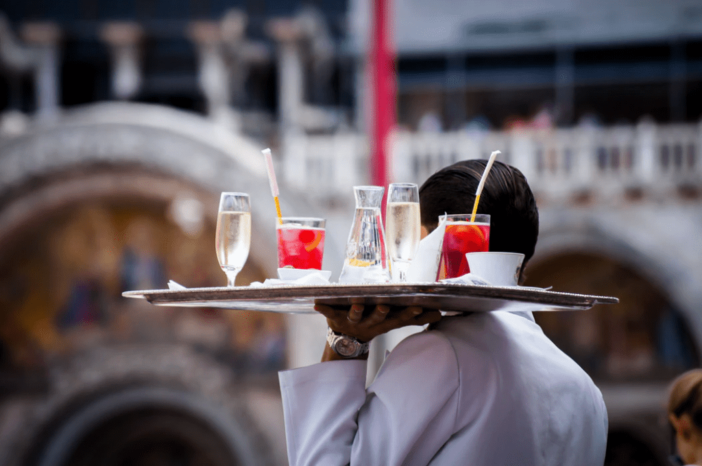 Waiter carrying drinks to a table