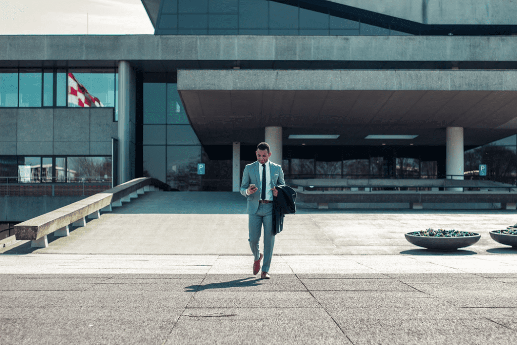 man wearing a suit walking out of office building while texting