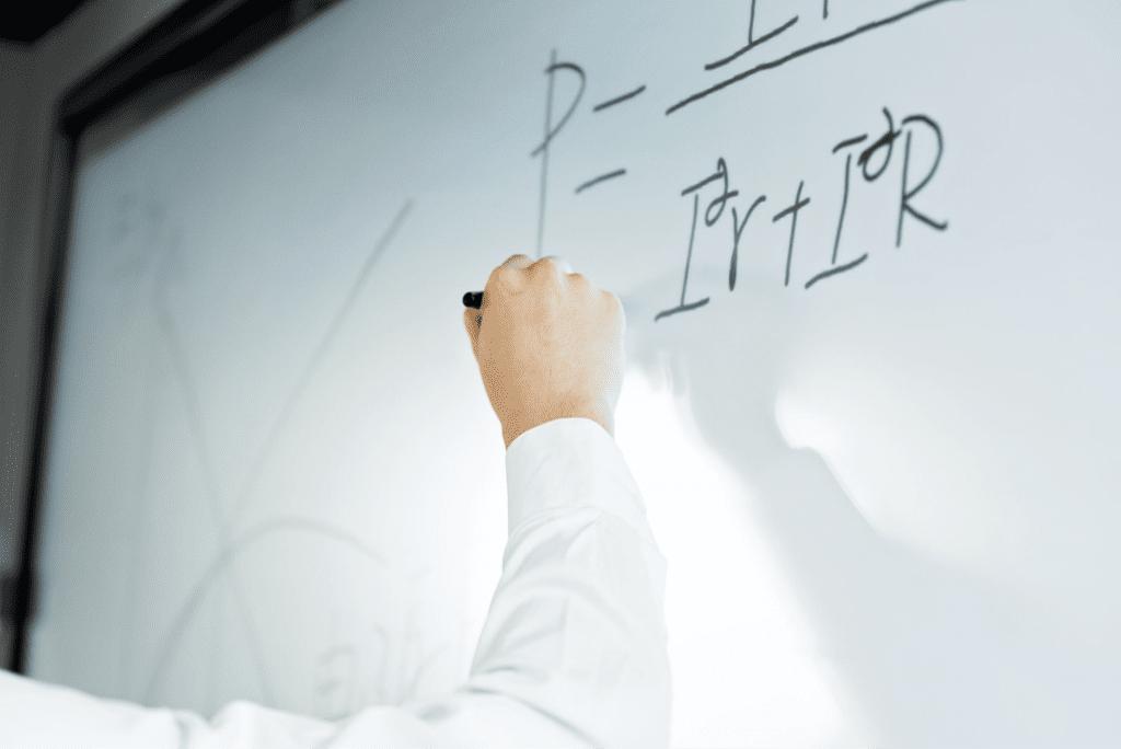Man writing on a formula on a whiteboard